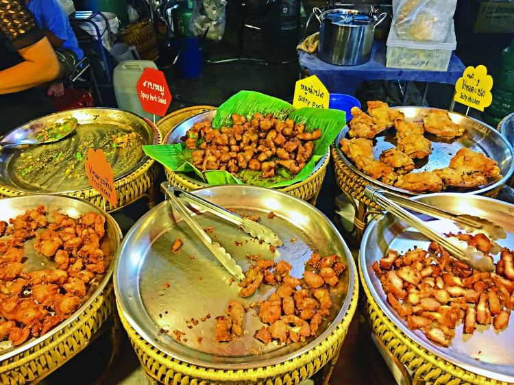 Local food stall at the night market. Varieties of Pork, Chicken and Fish are served with sticky plain rice